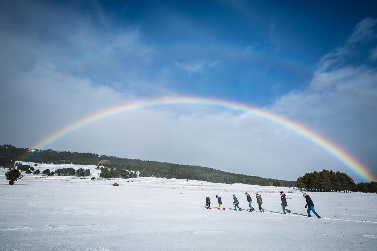 Photo d'une famille nombreuse à la neige avec un bel arc-en-ciel dans les Pyrénées