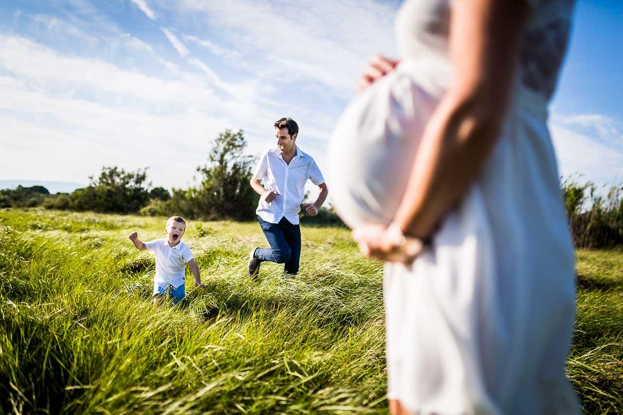 Photo d'un papa et son fils courant près de la maman enceinte lors d'une séance photo de grossesse à Perpignan