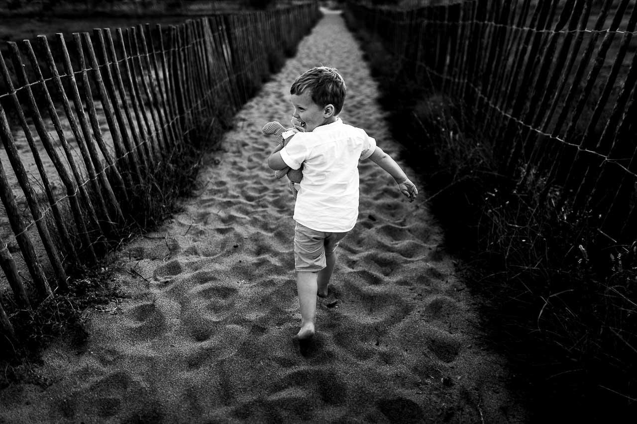Photo en noir et blanc d'un enfant courant sur la plage de Canet par Olivier Bolte photographe de famille