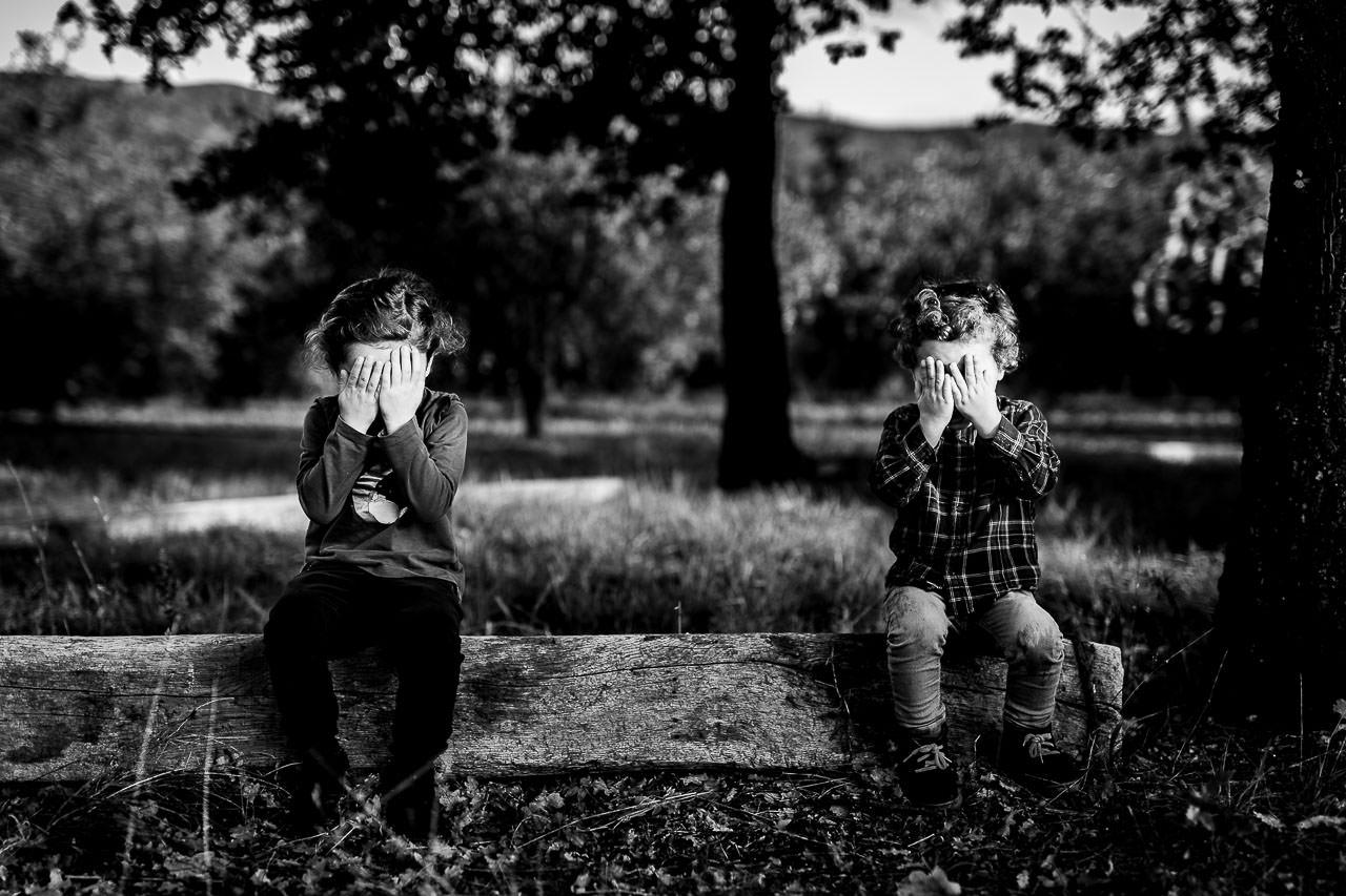 Photographie noir et blanc de deux enfants pendant un shooting famille