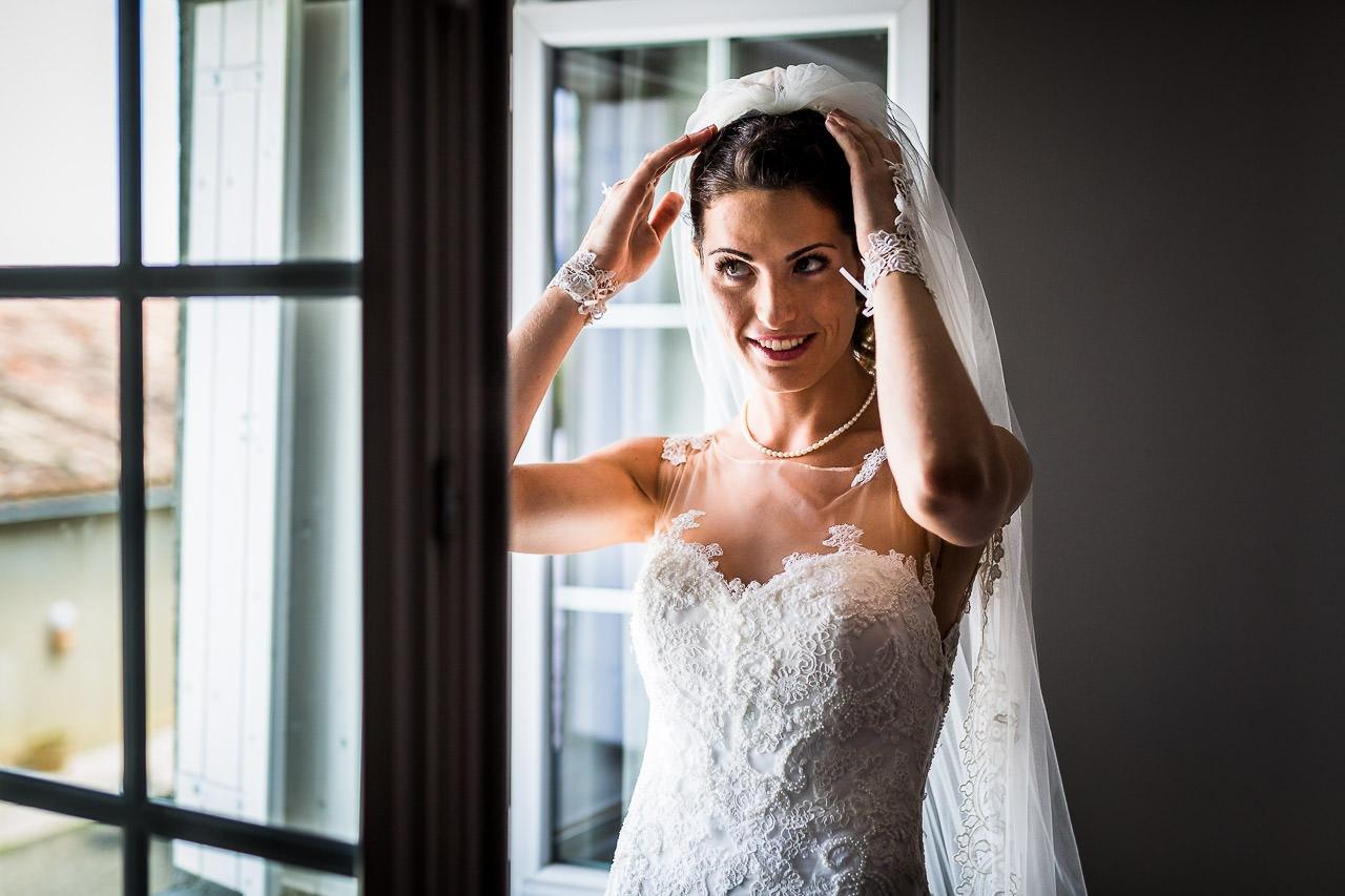 Photo d'une mariée ajustant son voile pendant les préparatifs de son mariage