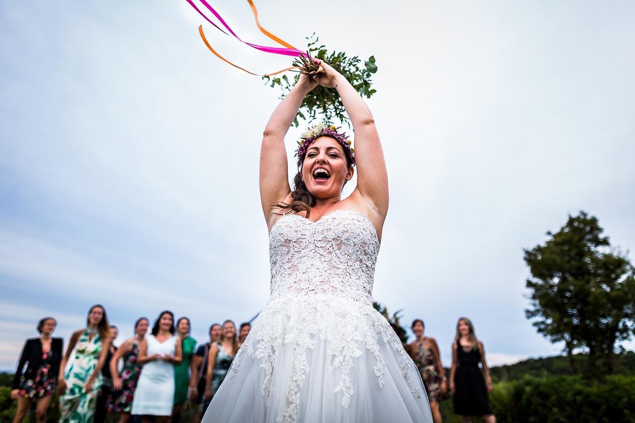 Photo sur le vif d'une mariée lançant son bouquet à son mariage au Château de Valmy dans le 66