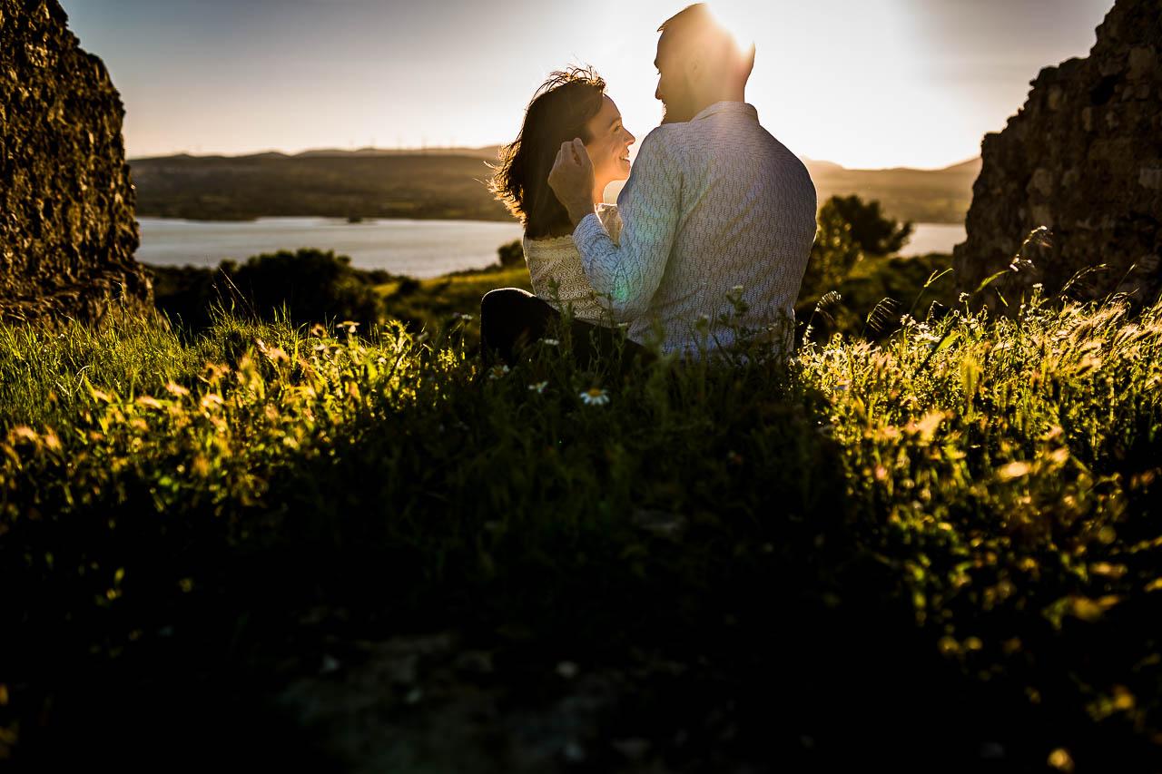 Un homme et sa copine assis dans l'herbe face au coucher de soleil pendant leur séance couple près de Perpignan