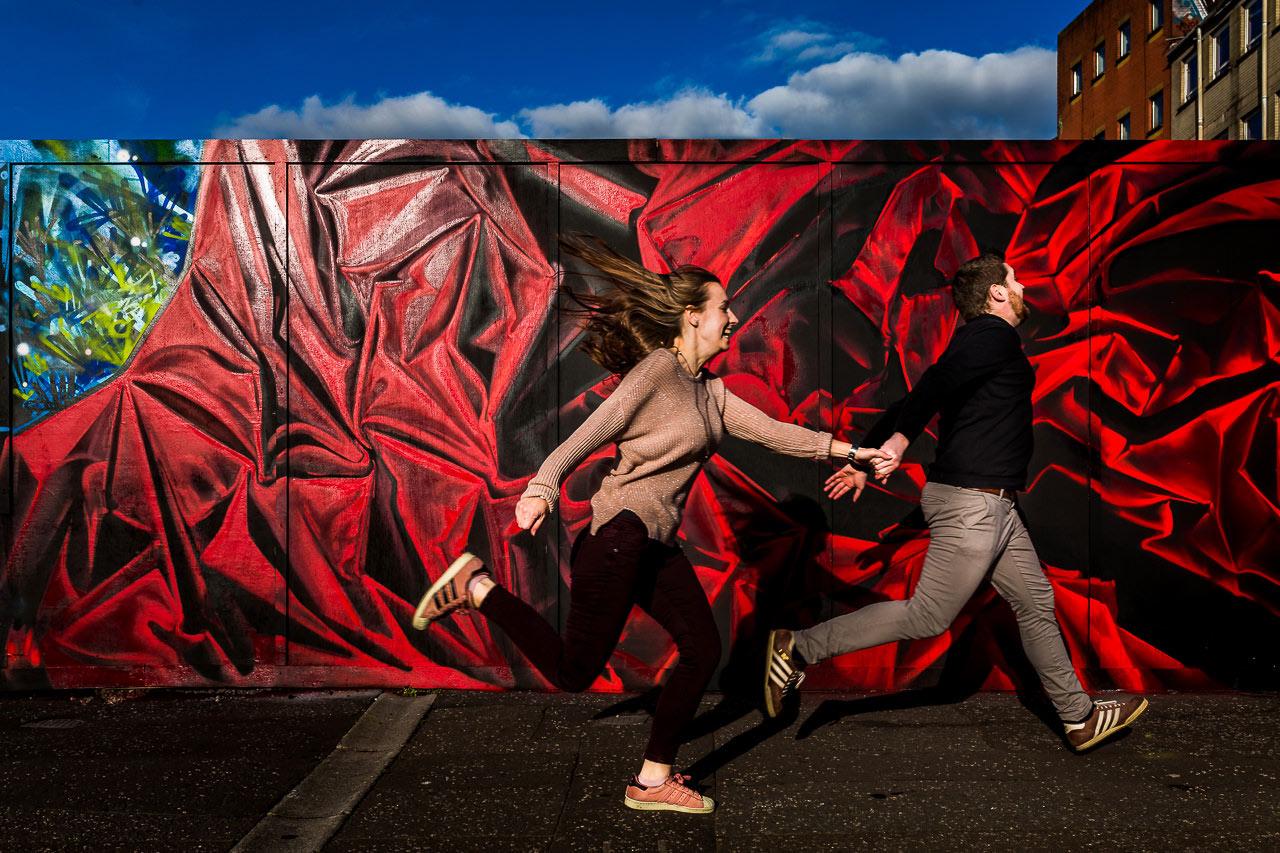 Photographie colorée et pleine de mouvement d'un couple qui court dans les rues de Belfast en Irlande