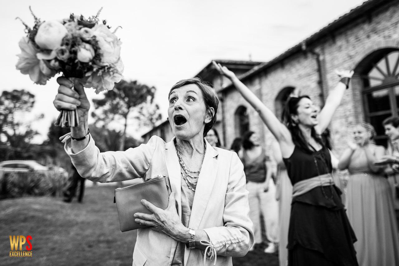 Photo d'une invitée attrapant le bouquet de la mariée lors d'un mariage au Domaine du Mas Conte