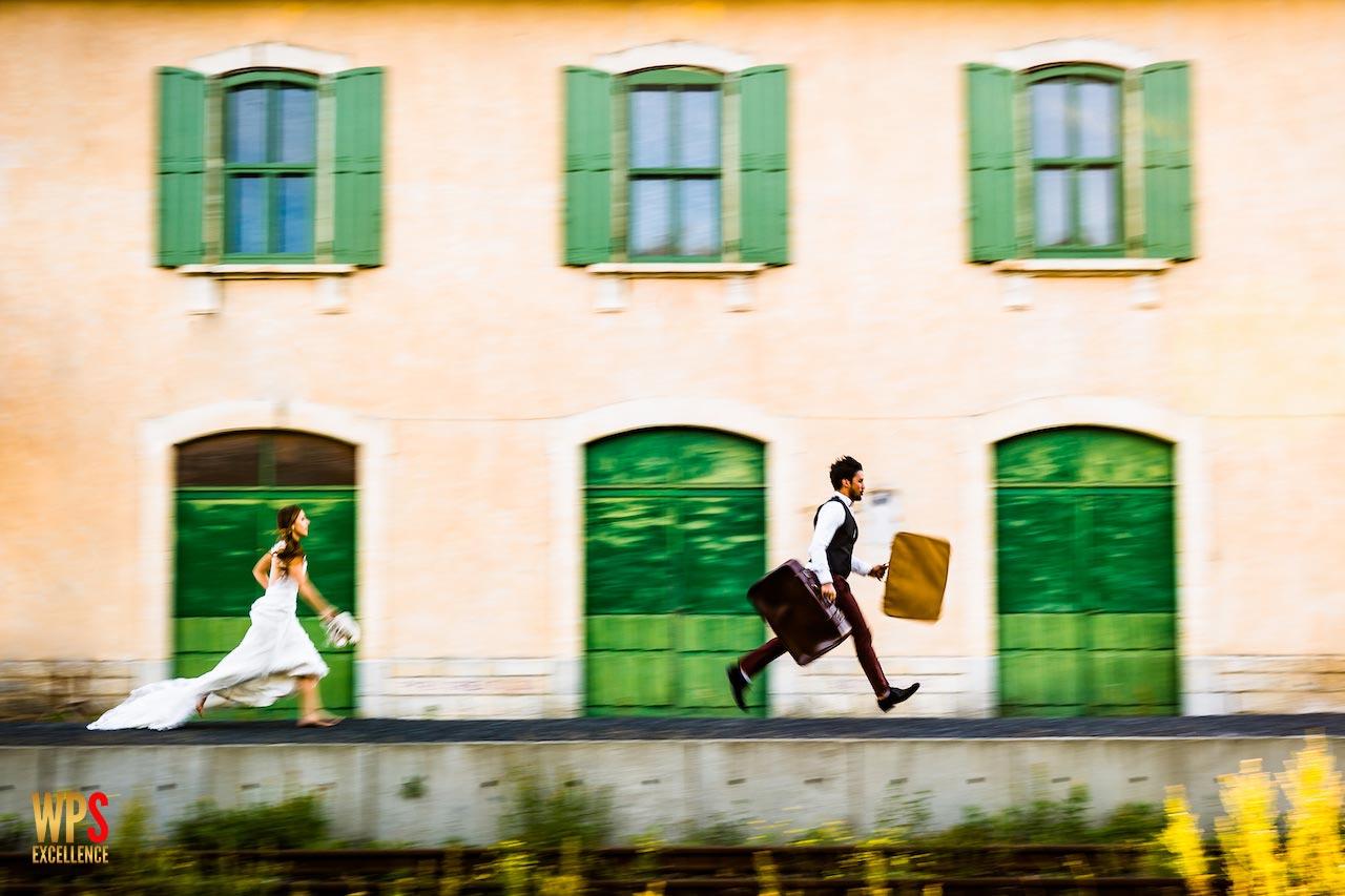 Couple de mariés courant sur le quai d'une gare avec des valises pendant leurs séance trash the dress dans les pyrénées orientales 66