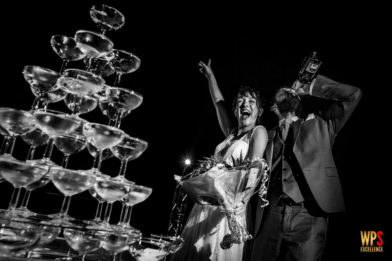 Couple de jeunes mariés devant la fontaine de champagne lors de leur mariage au Domaine de l'Ale près de Béziers