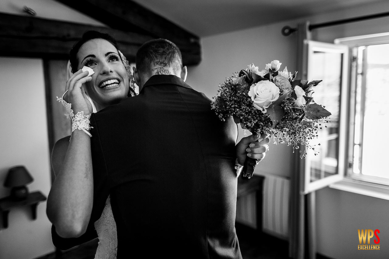 Photo pleine d'émotion d'une mariée pleurant dans les bras de son frère au Château d'Argères