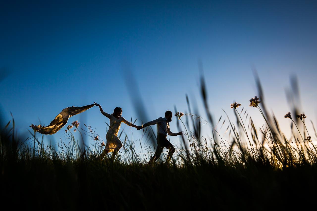 Couple courant dans les herbes au coucher de soleil pendant un shooting couple