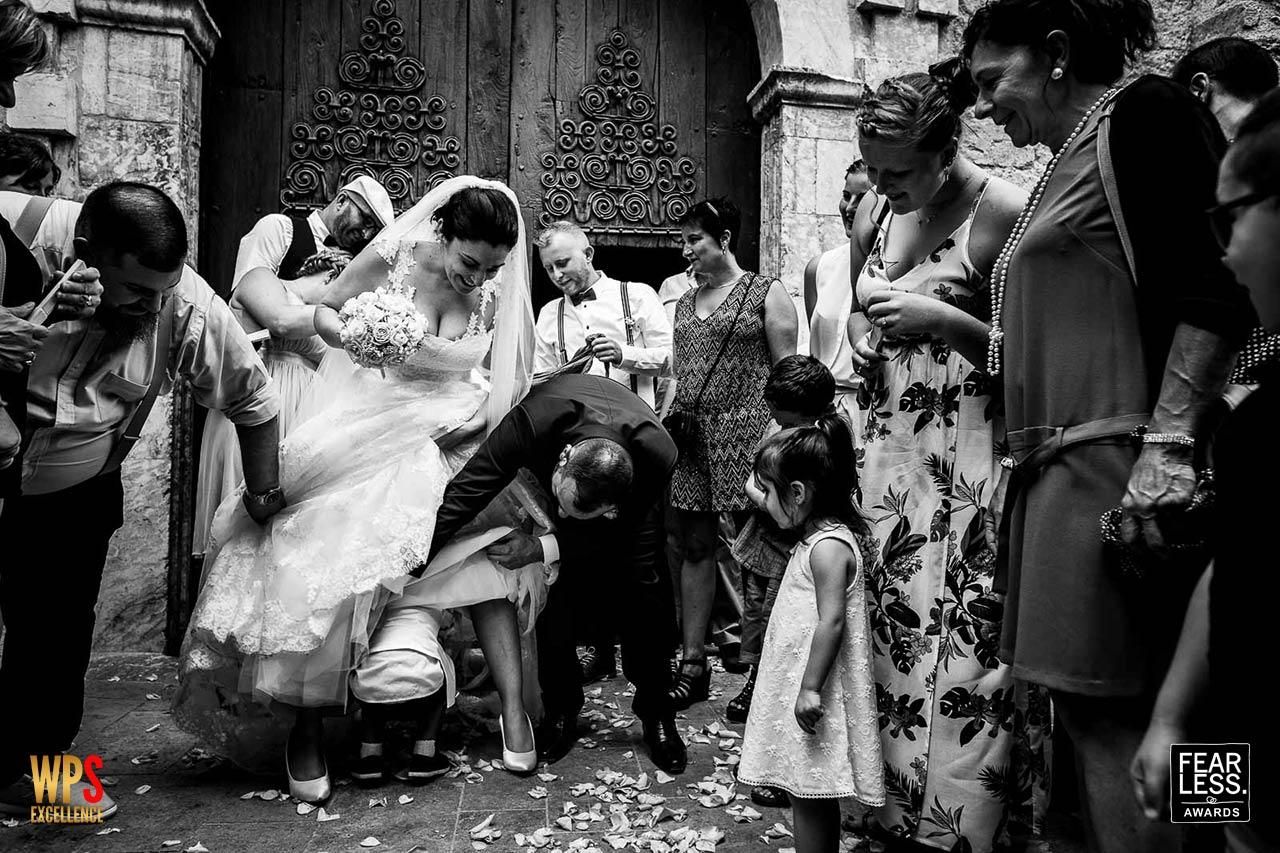 sortie d'église d'un mariage où un enfant passe sous la robe de la mariée