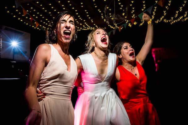 Mariée chantant à gorge déployée avec ses demoiselles d'honneur sur le dancefloor du château las collas