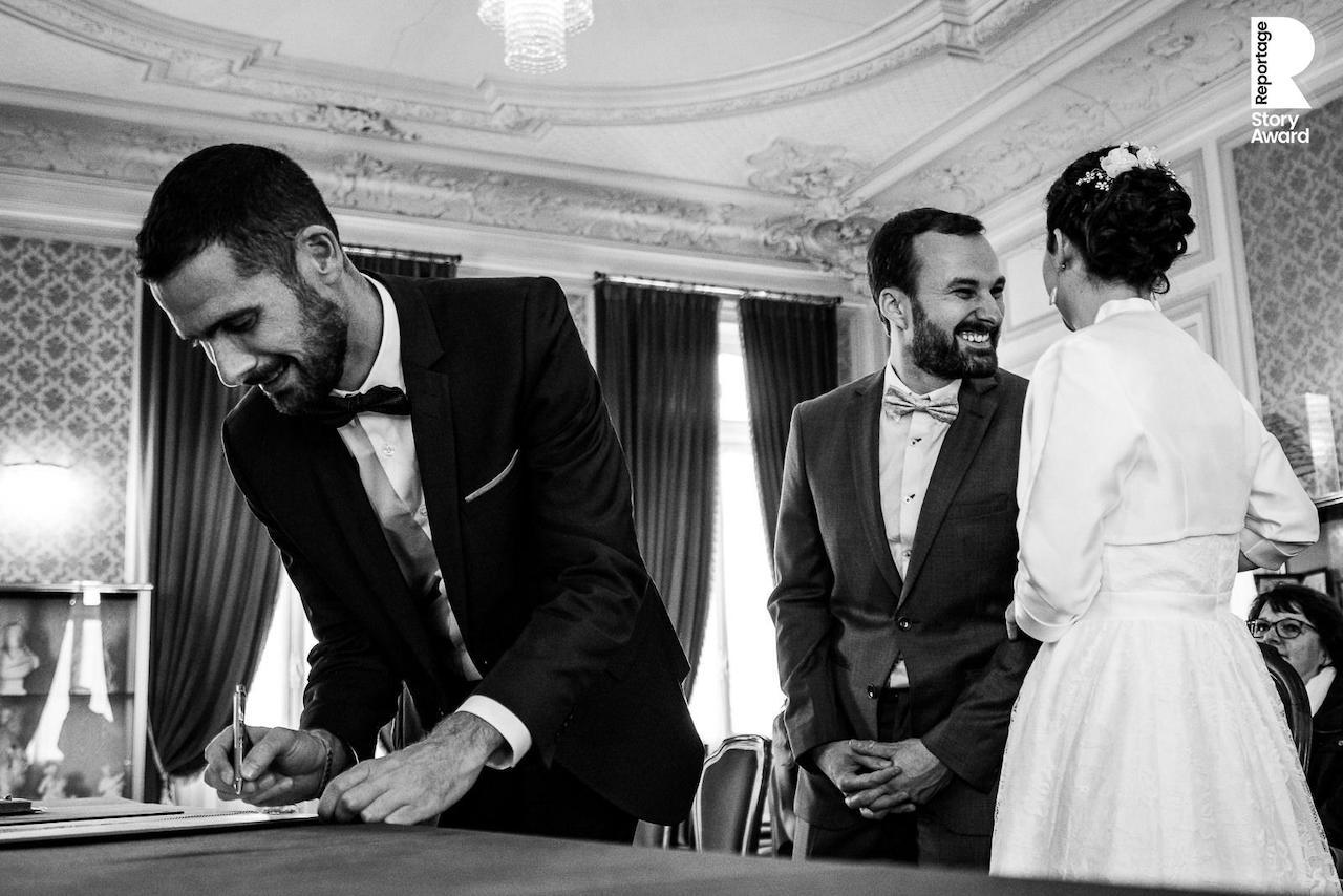 Regard complice des mariés pendant signature des registres à l'hôtel de ville