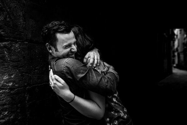 Couple d'amoureux s'enlaçant fort dans les rues de Barcelone pendant leur Love Session